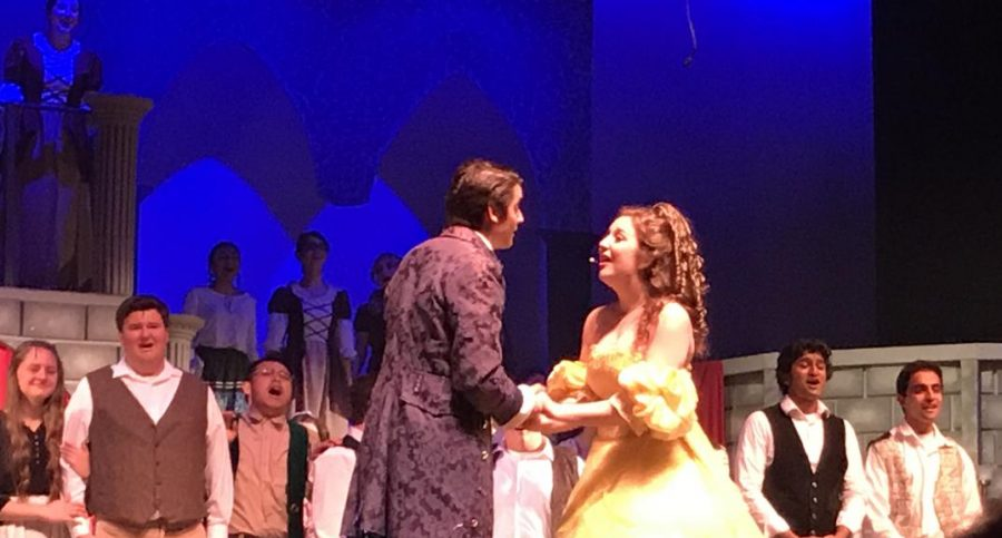 Sophomore Hazar Atay, as the Prince, and senior Hannah Chiappine, as Belle, close a duet along with other members of the cast during finale of Beauty & The Beast