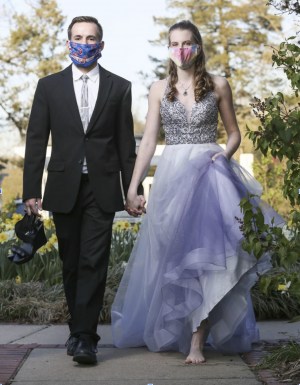 Two people wearing formal clothing and face masks.